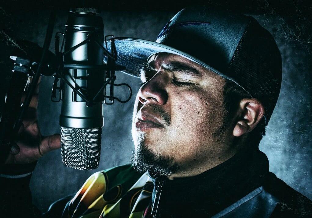 Mann mit Cap neben einem Studiomikrofon HipHop